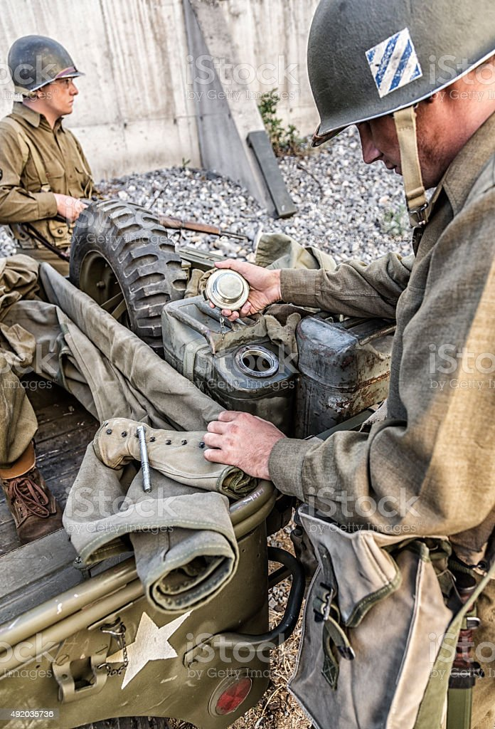 WWII US Army Soldier Checking Military Vehicle Gasoline Supply stock photo