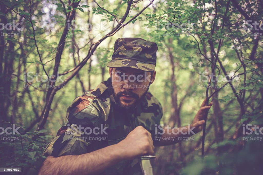 Army Soldier deep in forest stock photo