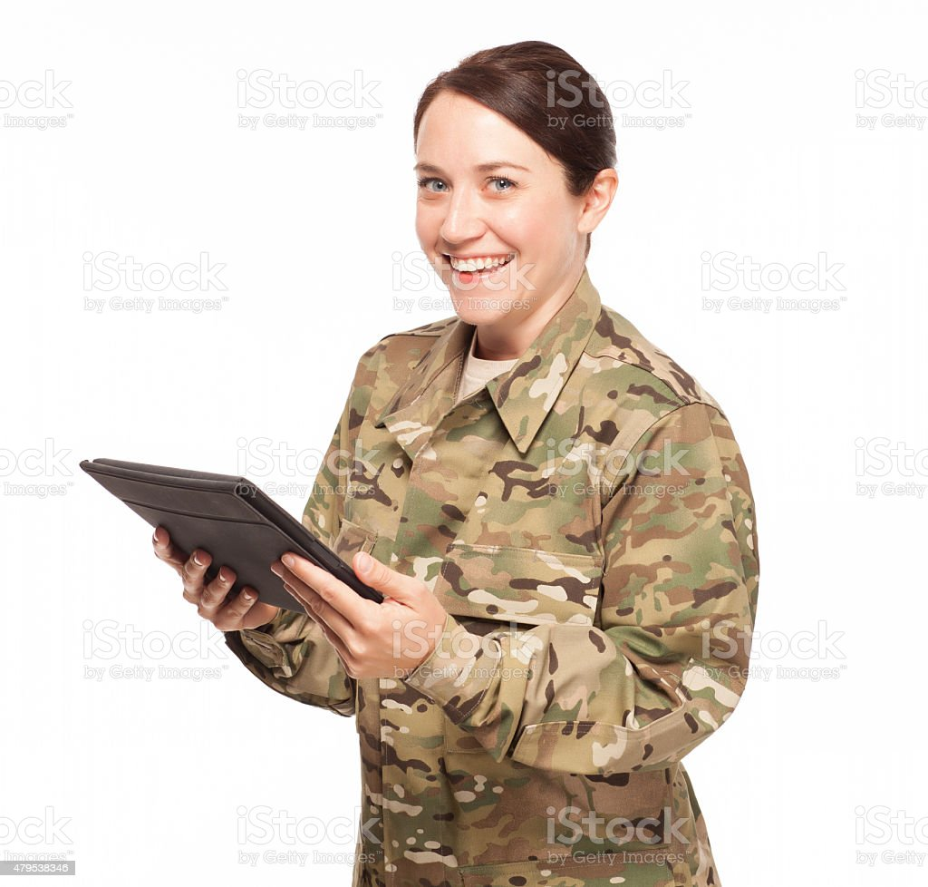 Army soldier holding digital tablet with a big grin. stock photo