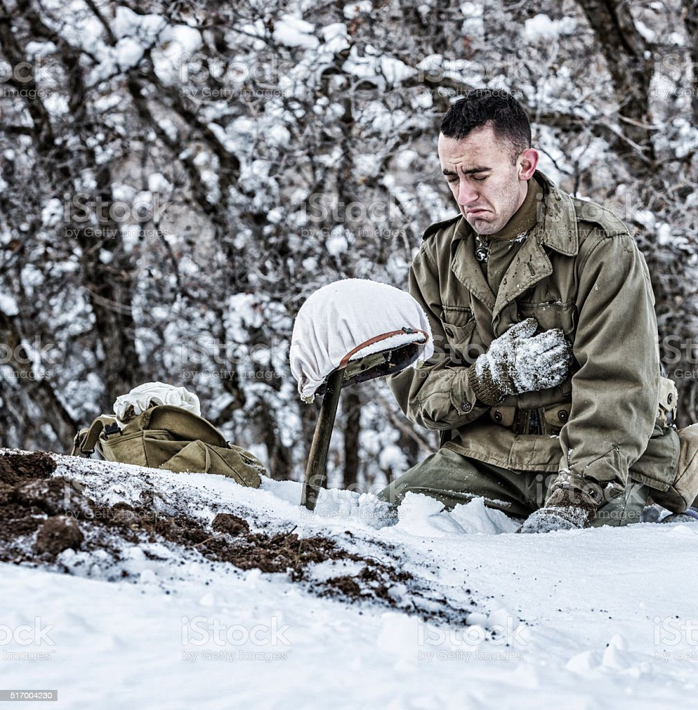 WWII US Army Soldier Kneeling Crying Mourning For Dead Buddy stock photo