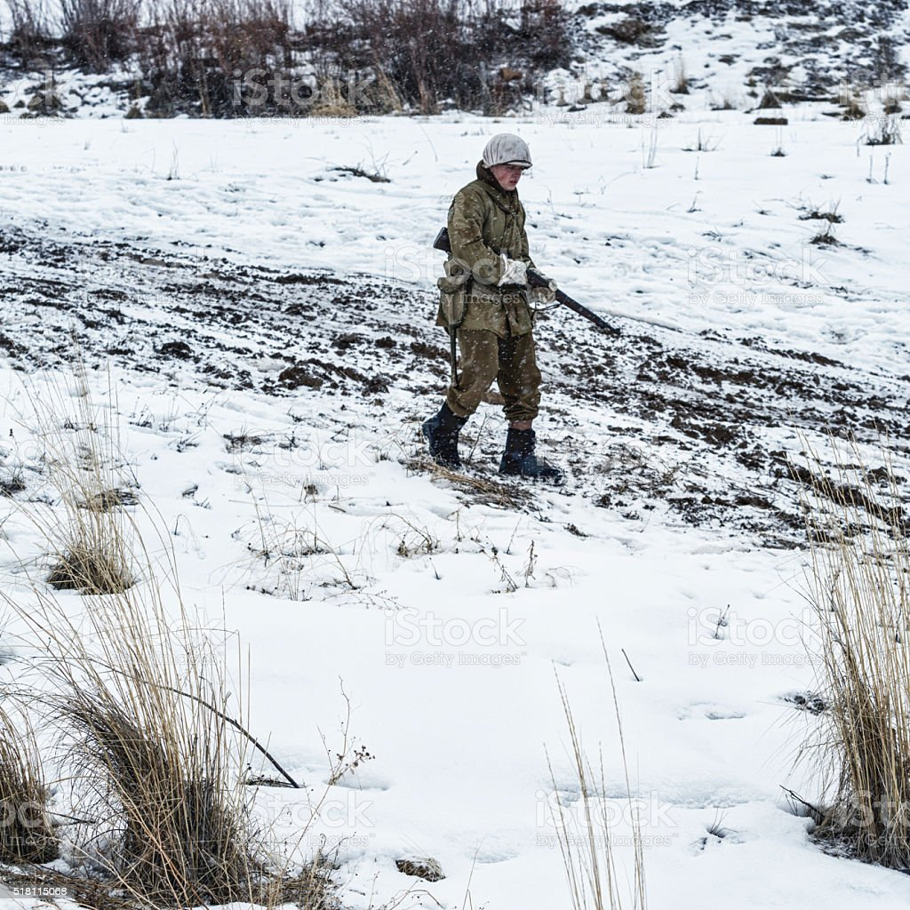 WWII US Army Soldier Patrolling Winter Snow Muddy Dirt Road stock photo