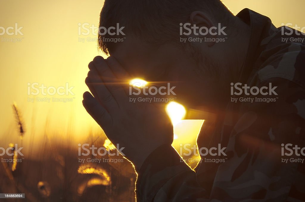 Army Soldier Praying Outside in Field at Sunset stock photo