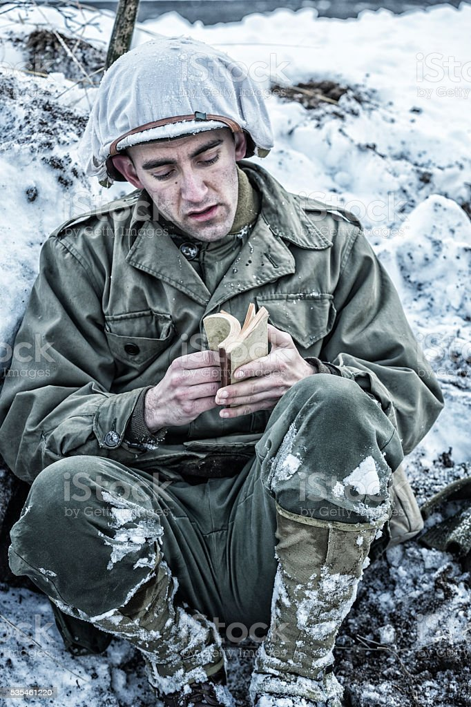 WWII US Army Soldier Searching New Testament Bible Scripture Pages stock photo