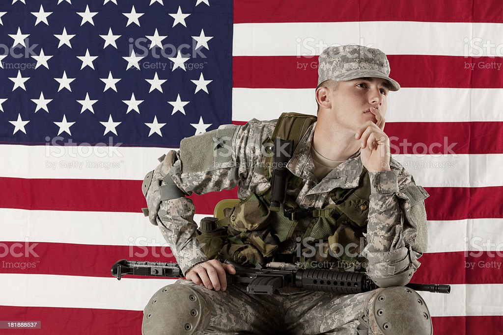 Army soldier sitting in front of American flag royalty-free stock photo