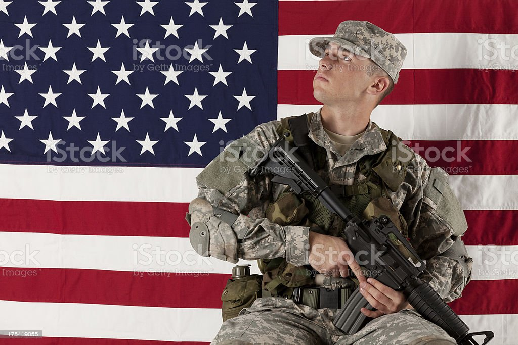 Army soldier sitting in front of an American flag royalty-free stock photo