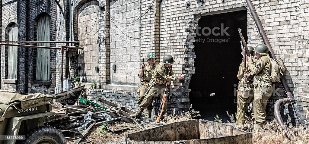 WWII US Army Soldier Throwing Hand Grenade Into Building stock photo