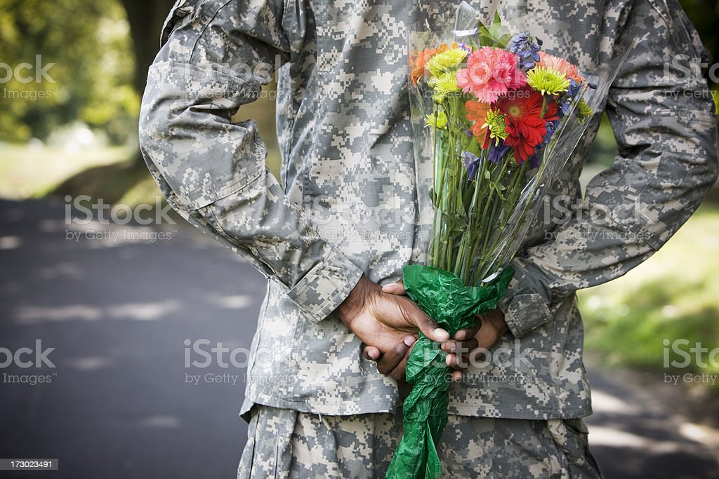 Army Soldier with Flower Bouquet Behind Back, Copy Space royalty-free stock photo