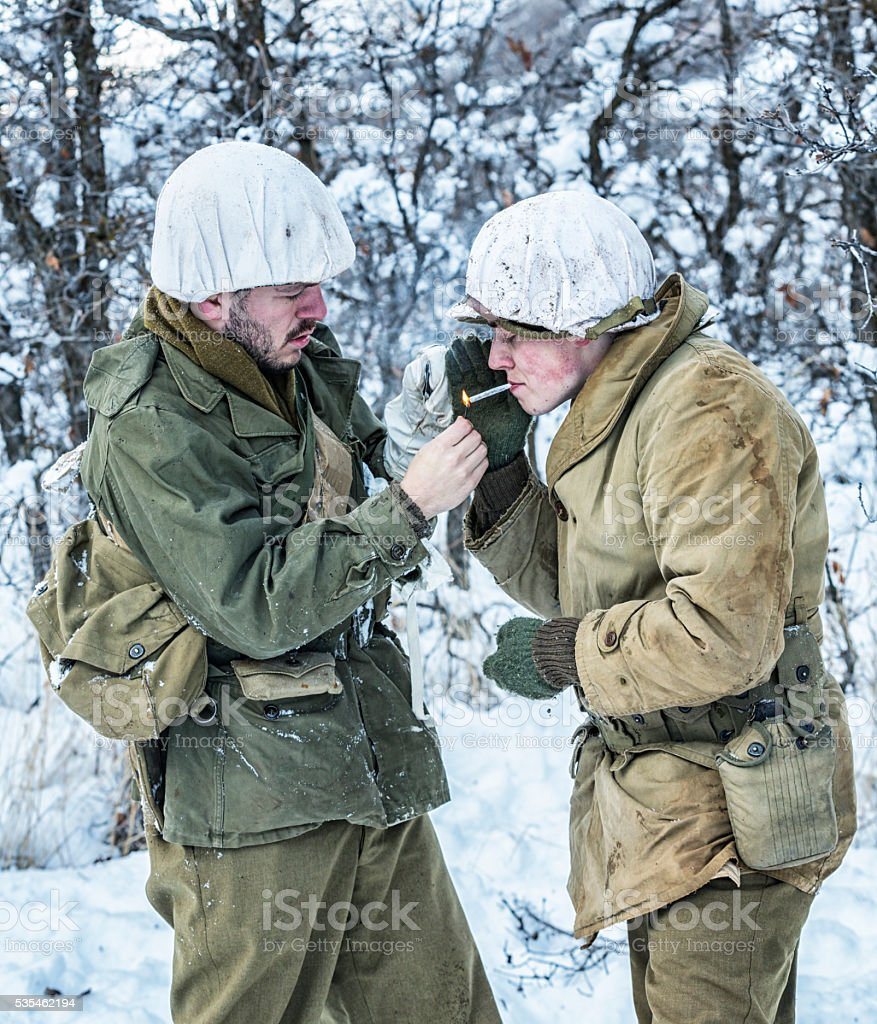 WWII US Army Soldiers Lighting Cigarette in Winter Wind stock photo
