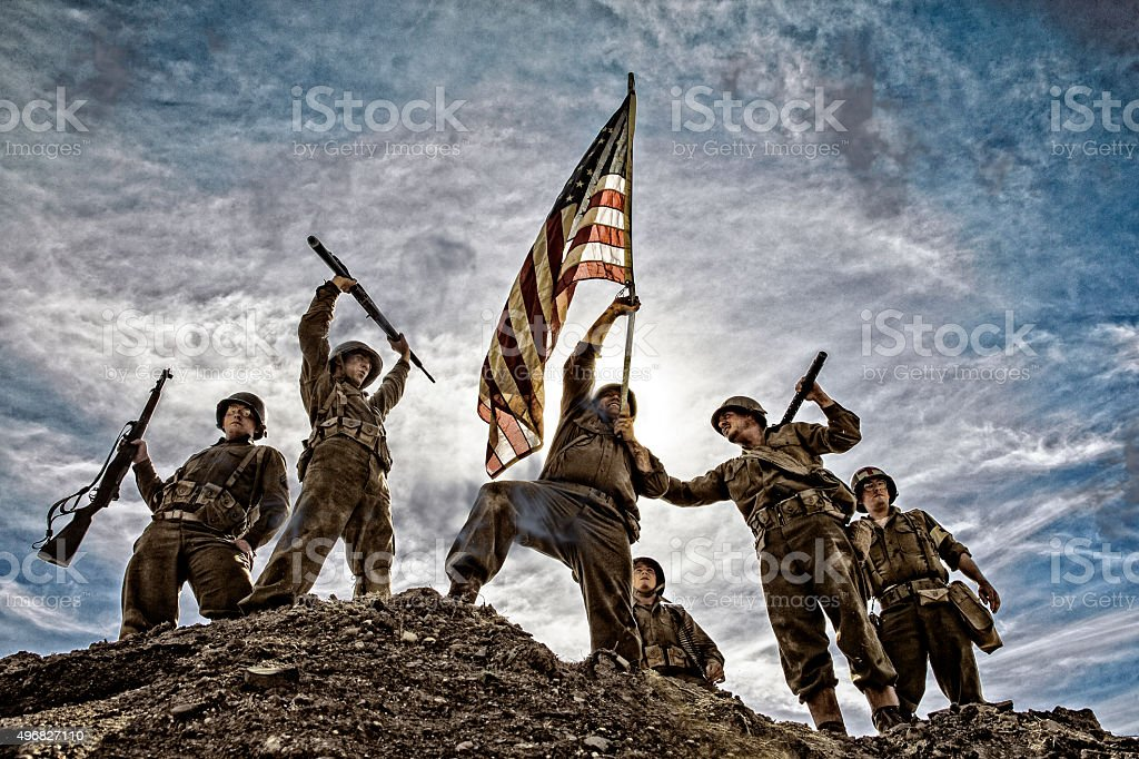 US Army Soldiers on hill with American Flag stock photo