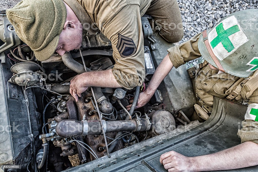 WWII US Army Soldiers Repairing Military Vehicle Engine stock photo