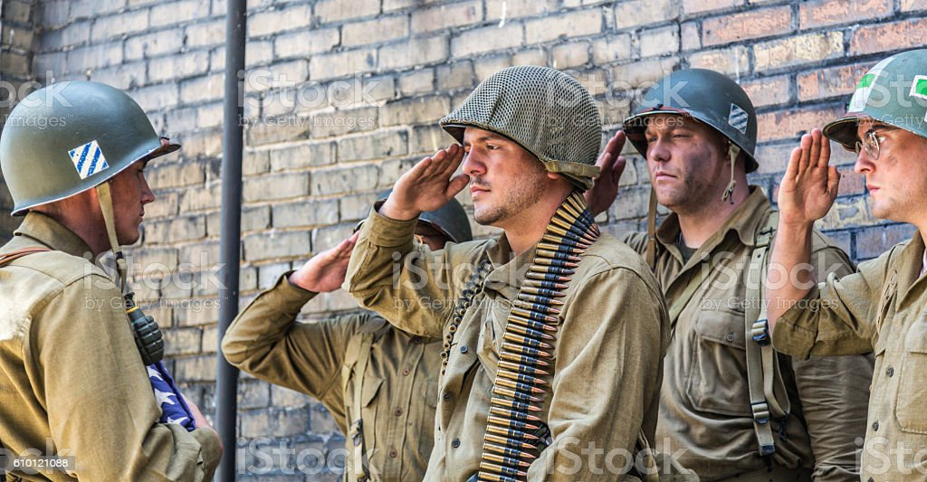 WWII US Army Soldiers Saluting Folded American Flag stock photo