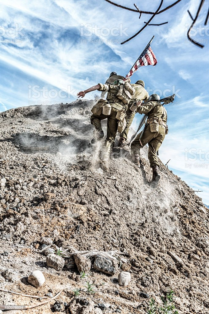 WWII US Army Soldiers Scrambling Up Hill With American Flag stock photo
