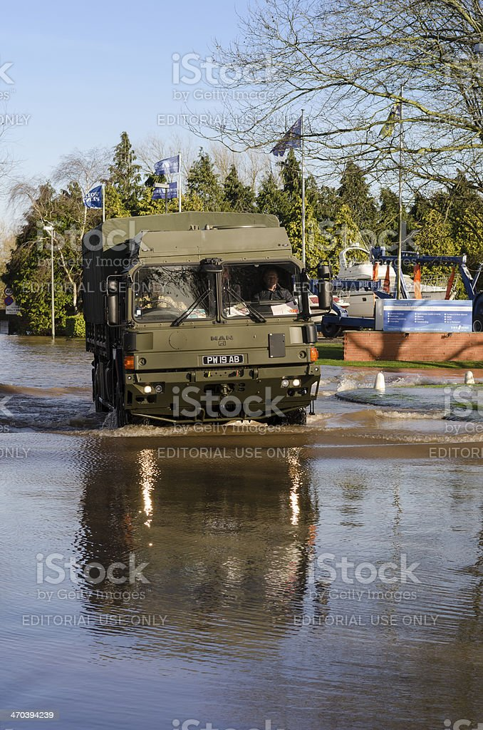 Army truck drives down flooded road stock photo