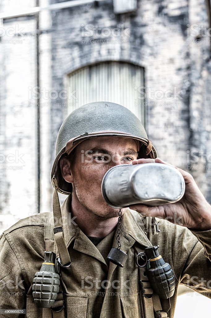 US Army World War II Soldier Drinking Water Canteen Close-Up stock photo