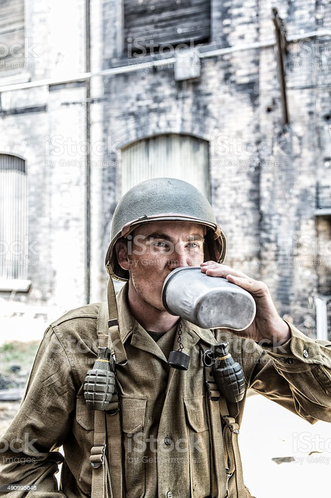 US Army WW II Soldier Drinking Water From Metal Canteen stock photo