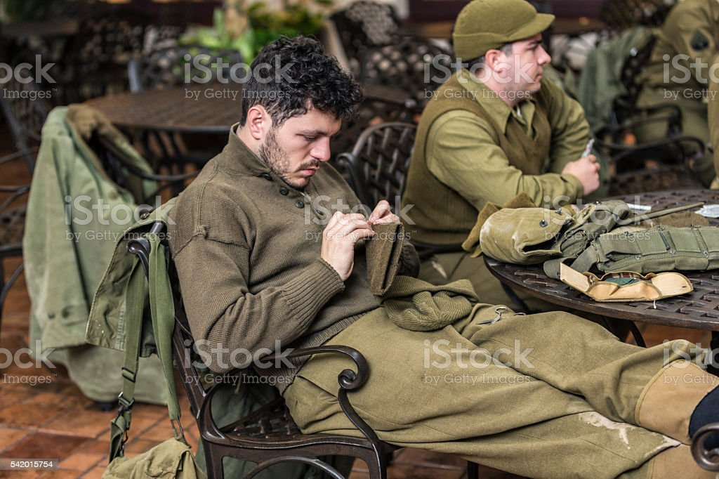 US Army WWII Soldier Relaxing Sewing Leather Glove stock photo