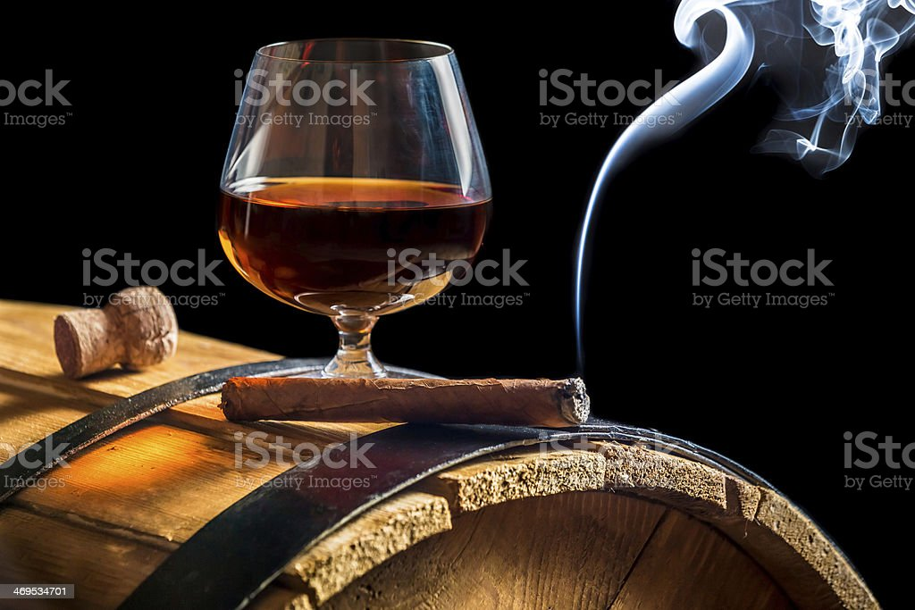 Aroma of Cuban cigars and cognac on black background stock photo