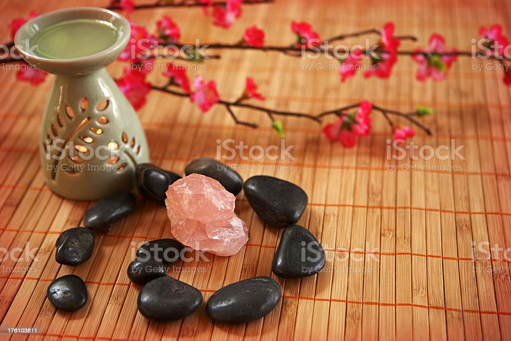 \'An aromatherapy oil burner, next to a spiral of black pebbles, and...