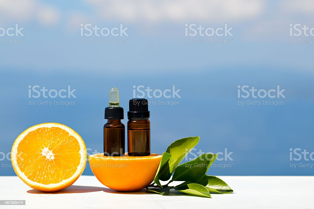 Aromatherapy essential oils in bottles with oranges stock photo