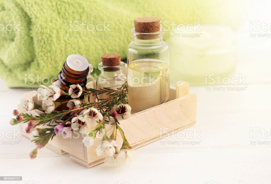Aromatherapy oils set in wooden box with flowers stock photo