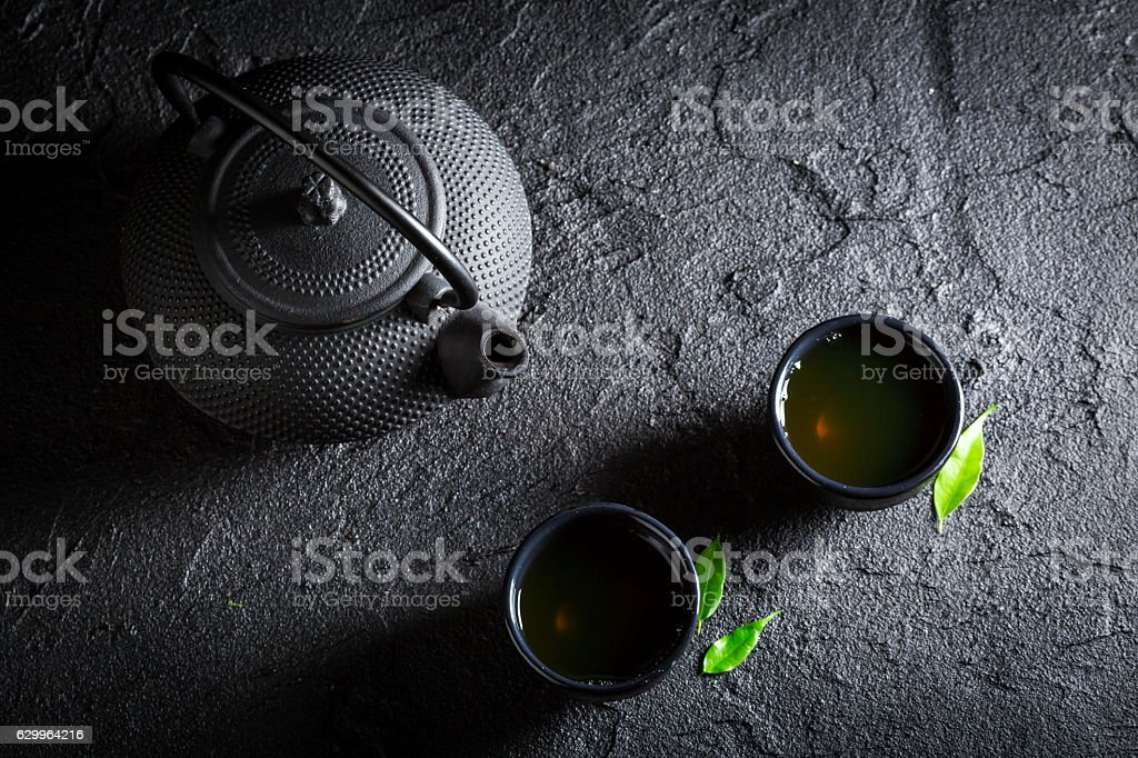 Aromatic green tea with teapot and cup on black rock stock photo