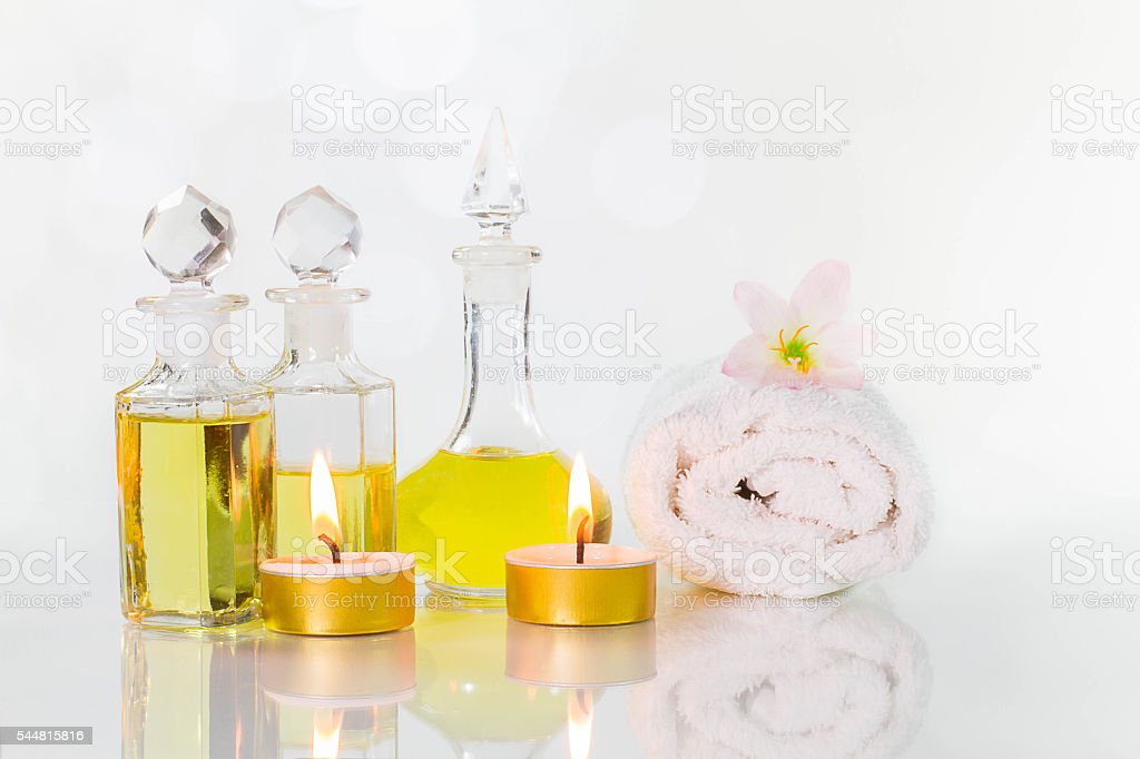 Aromatic oil  bottles with candles, flowers, towel on white background stock photo