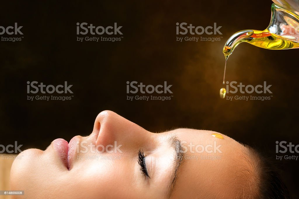 Aromatic oil dripping on female face. stock photo
