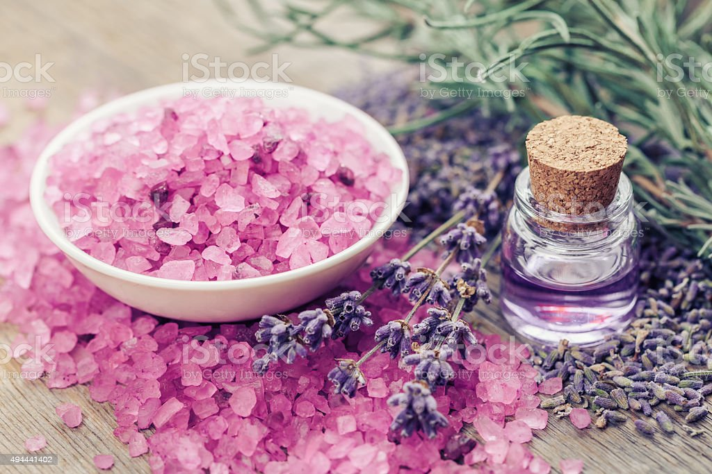 Aromatic sea salt, bottle of essential oil and lavender flowers. stock photo