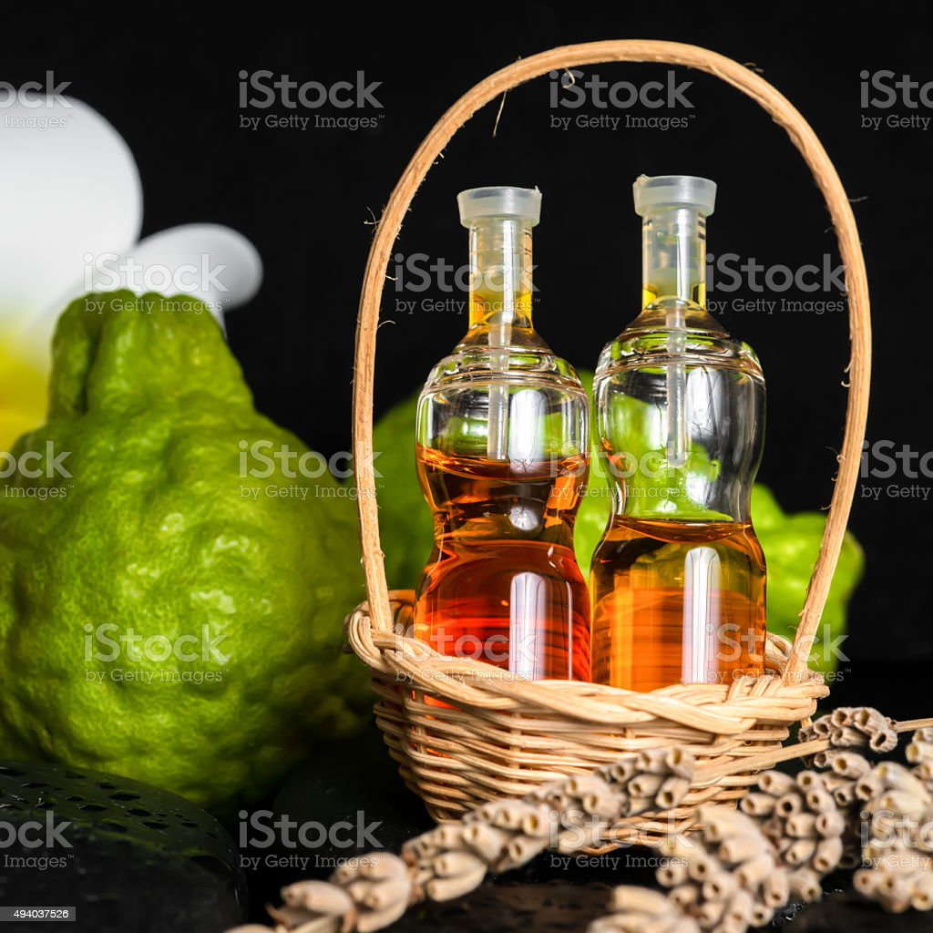 Aromatic spa concept of bottles essential oil in basket, flower, stock photo