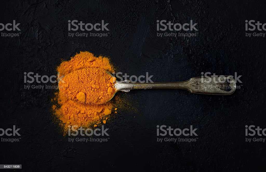 aromatic turmeric in a vintage spoon on a black background stock photo