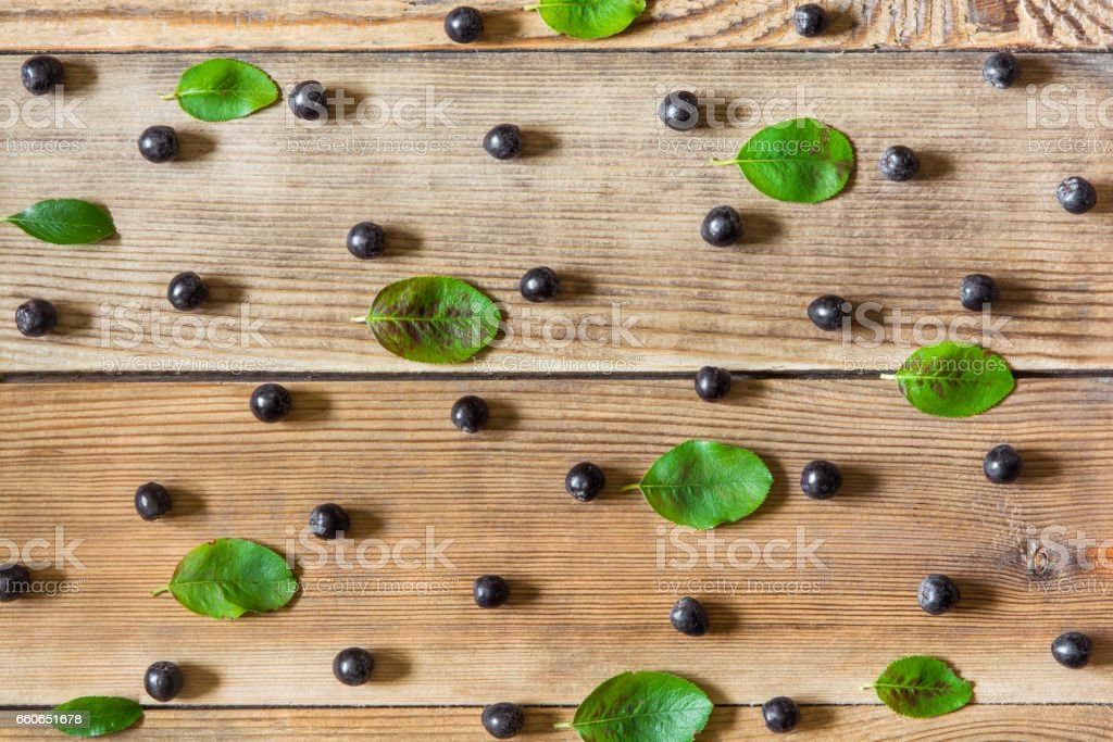 Aronia berries (black chokeberry) and leaves on wooden background stock photo
