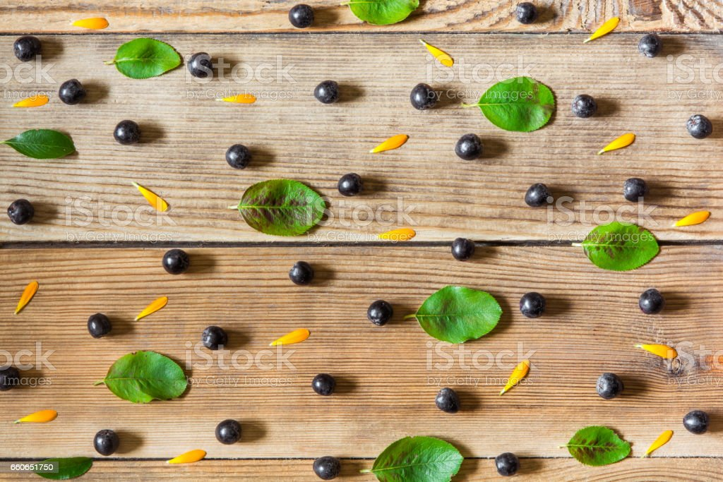 Aronia berries (black chokeberry), calendula petals and leaves on wooden background stock photo