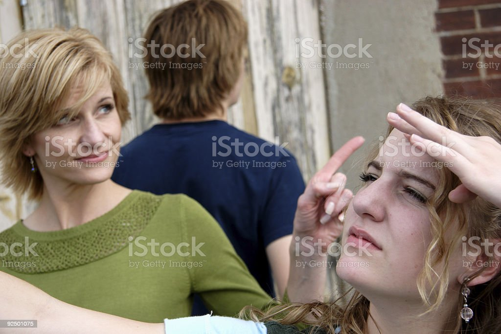 around here somewhere    - middle aged woman and teens stock photo