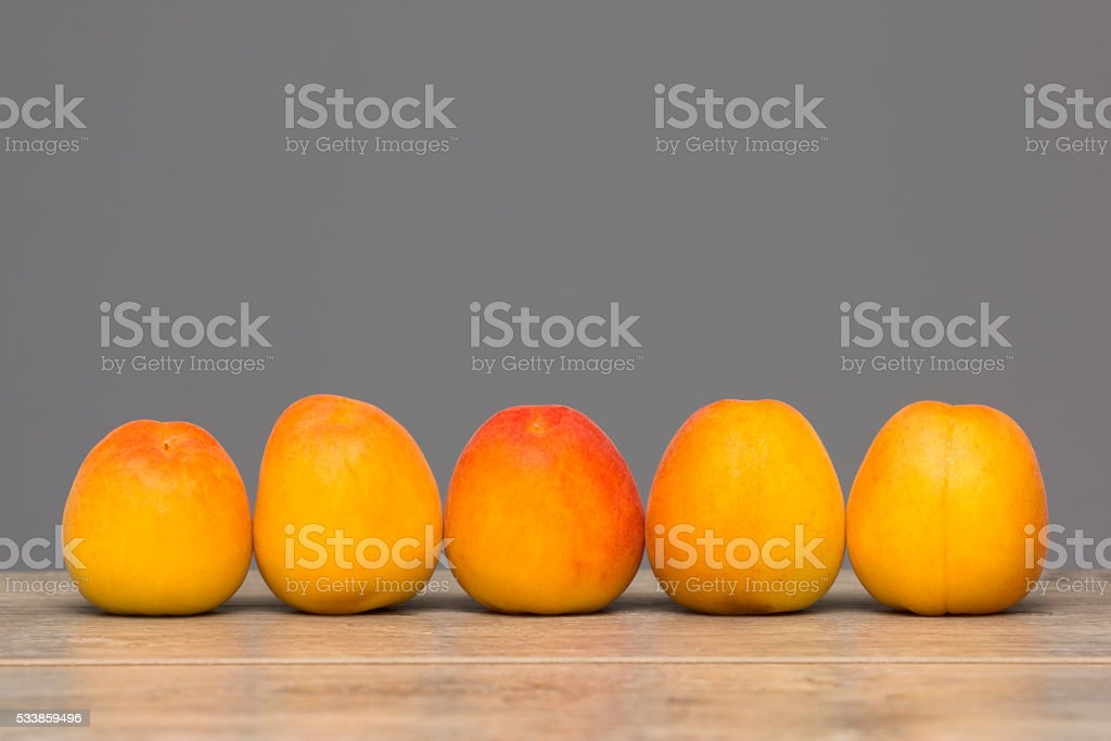 Arranged apricots on wooden textured table stock photo