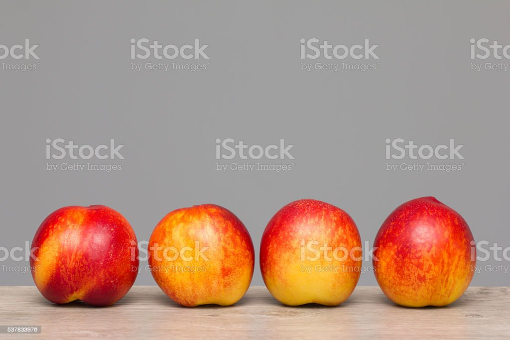 Arranged nectarine on wooden textured table stock photo