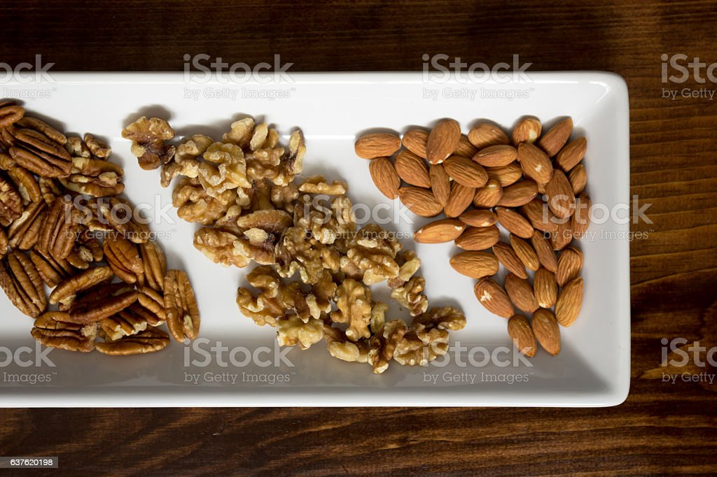 Arranged Pecans, Walnuts, and Almonds on White Tray, Close stock photo