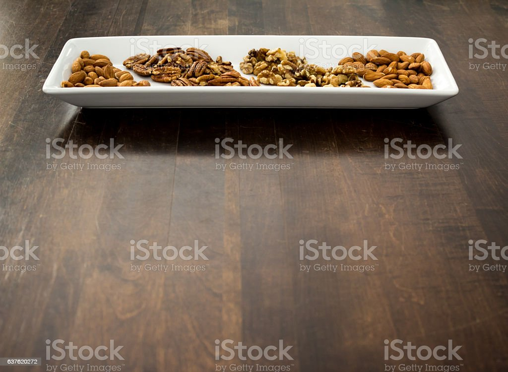 Arranged Pecans, Walnuts, and Almonds on White Tray, copy space. stock photo