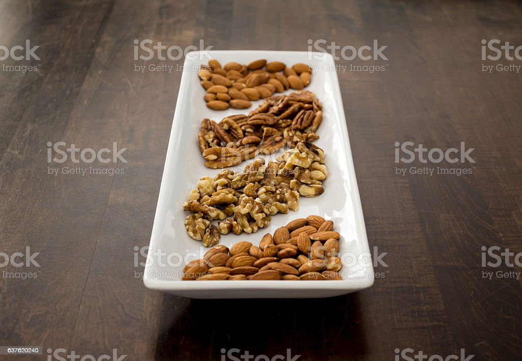 Arranged Pecans, Walnuts, and Almonds on White Tray, perspective stock photo