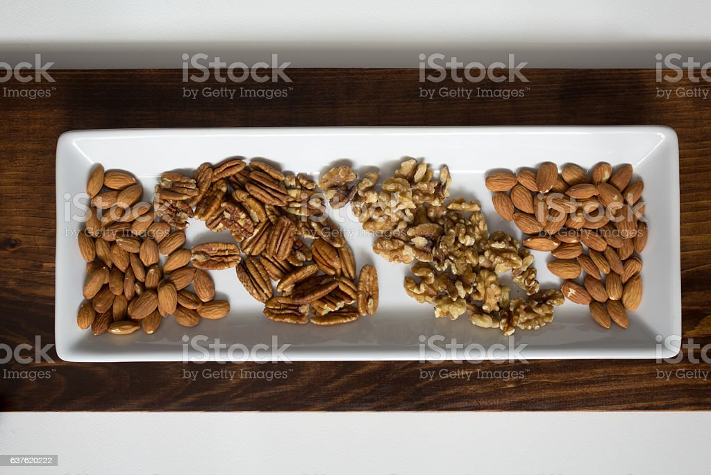Arranged Pecans, Walnuts, and Almonds on White Tray stock photo