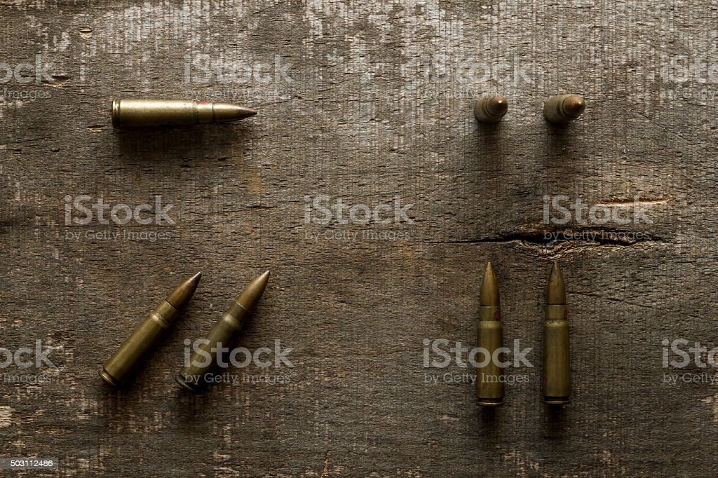 Arranged rifle bullets on old wooden plank stock photo