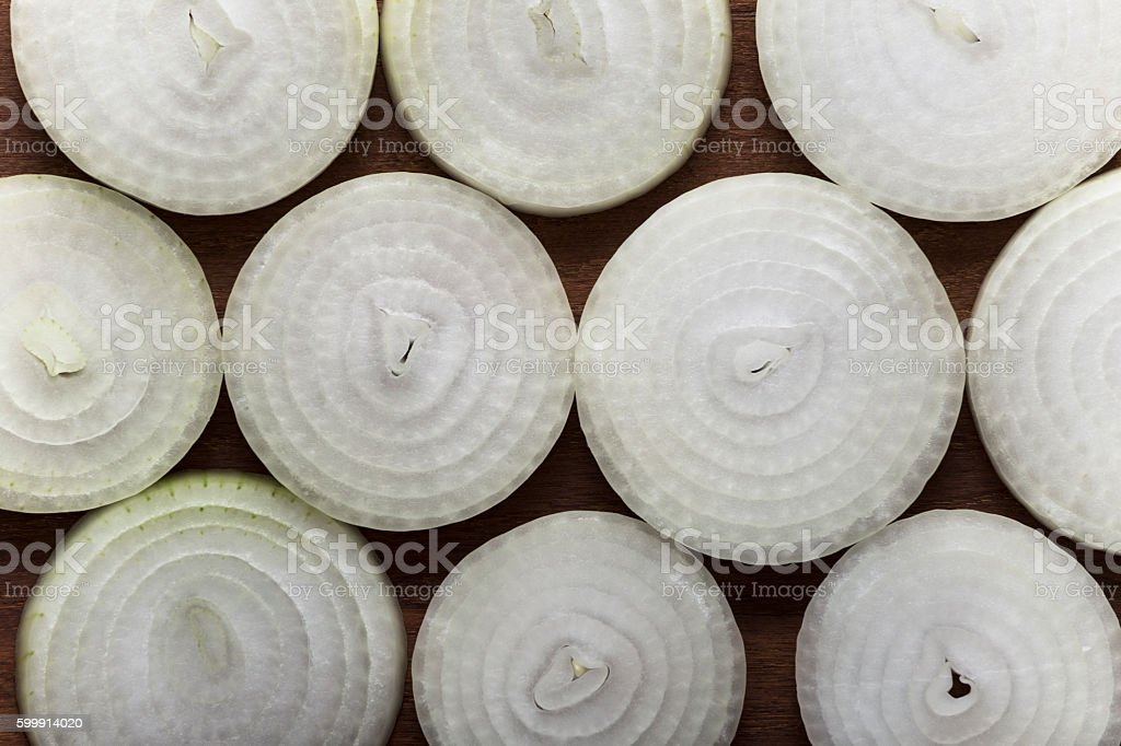 Arranged rings of sliced onion on wooden table stock photo