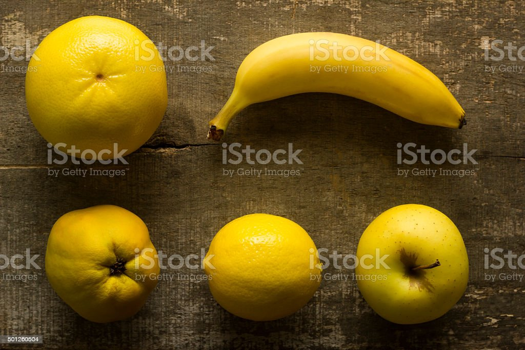 Arranged yellow fruits on old wooden table stock photo