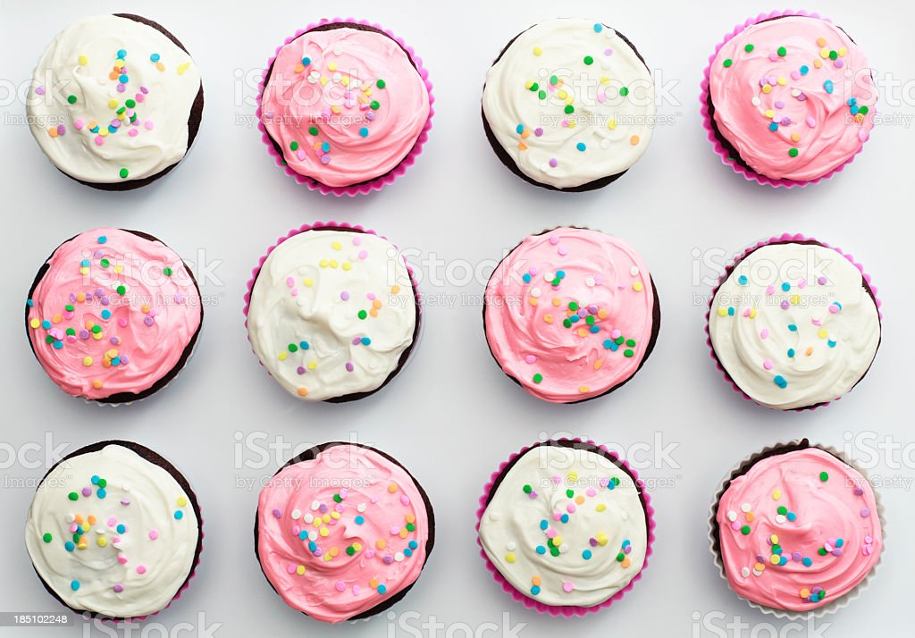 Arrangement of 12 pink and white sprinkled cupcakes stock photo