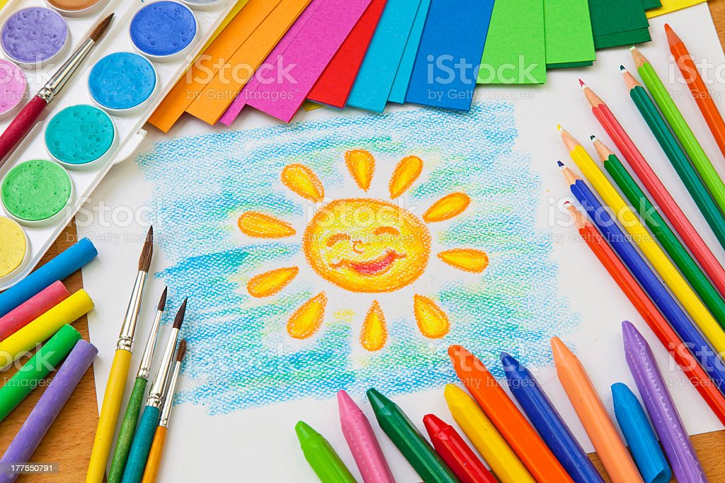 Arrangement of hand drawn sun surrounded by art supplies royalty-free stock photo