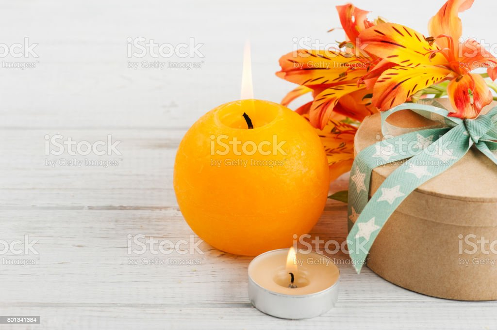 Arrangement of orange lily flowers and candle, gift box stock photo