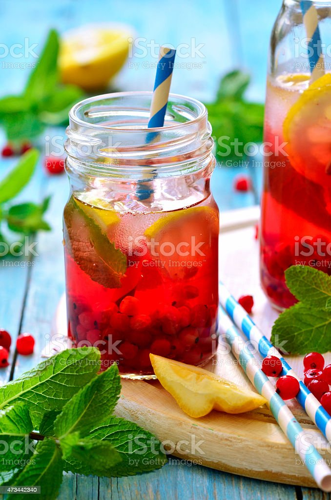 Arrangement of redcurrant iced tea with lemon and mint stock photo