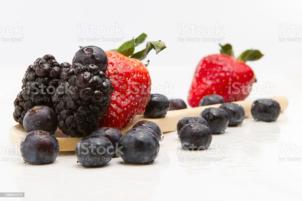 Arrangement of strawberries, blackberries and blueberries on a wooden spoon. stock photo