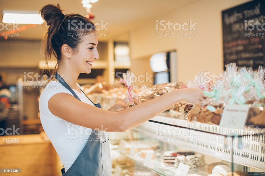 Arranging cookies in the bakery stock photo