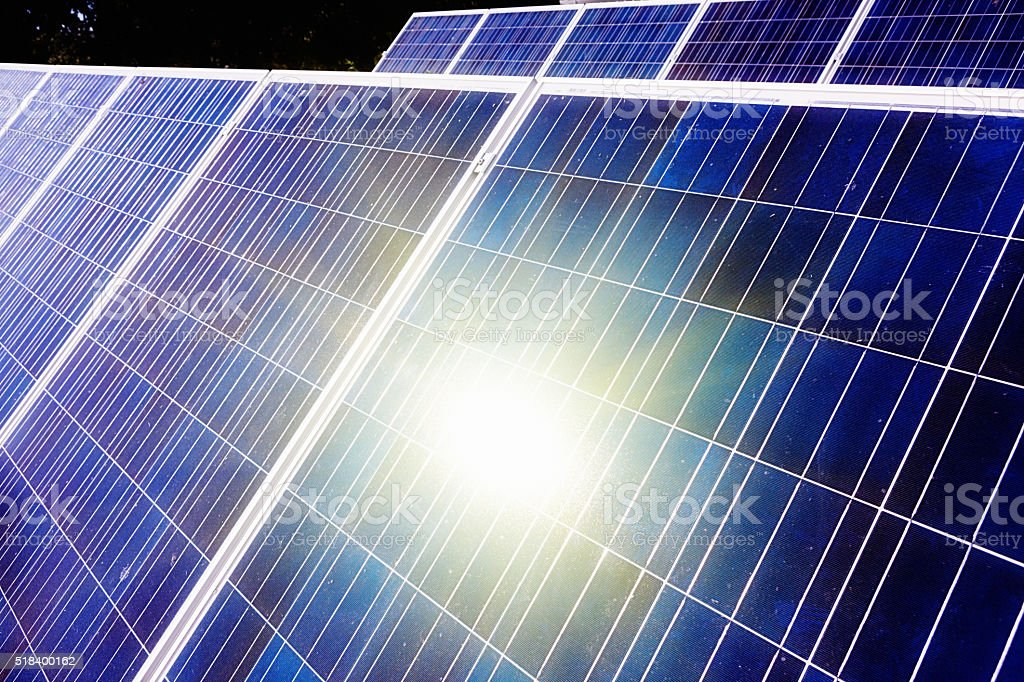 Array of solar panels reflecting the sun which powers them stock photo