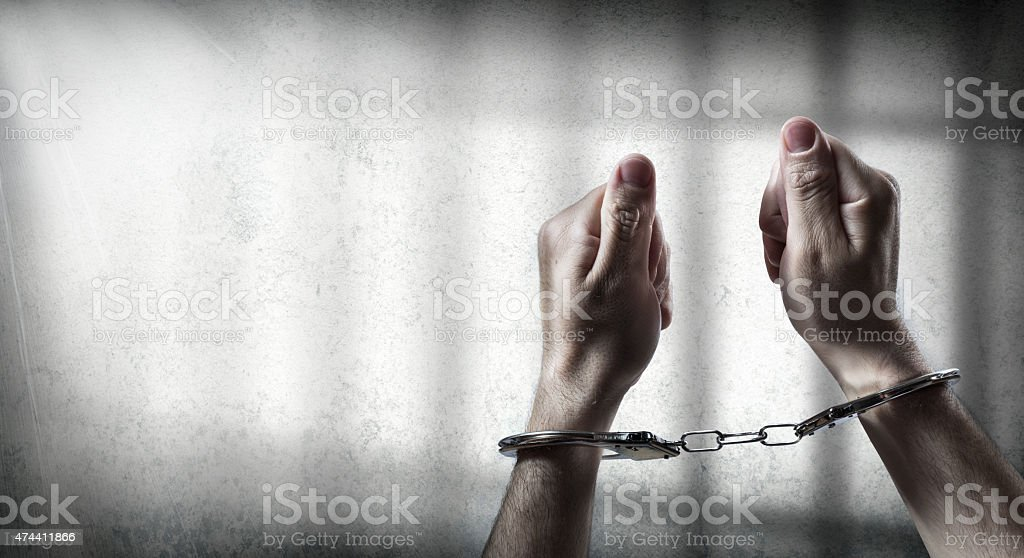 arrest  - man handcuffed in cell prison stock photo